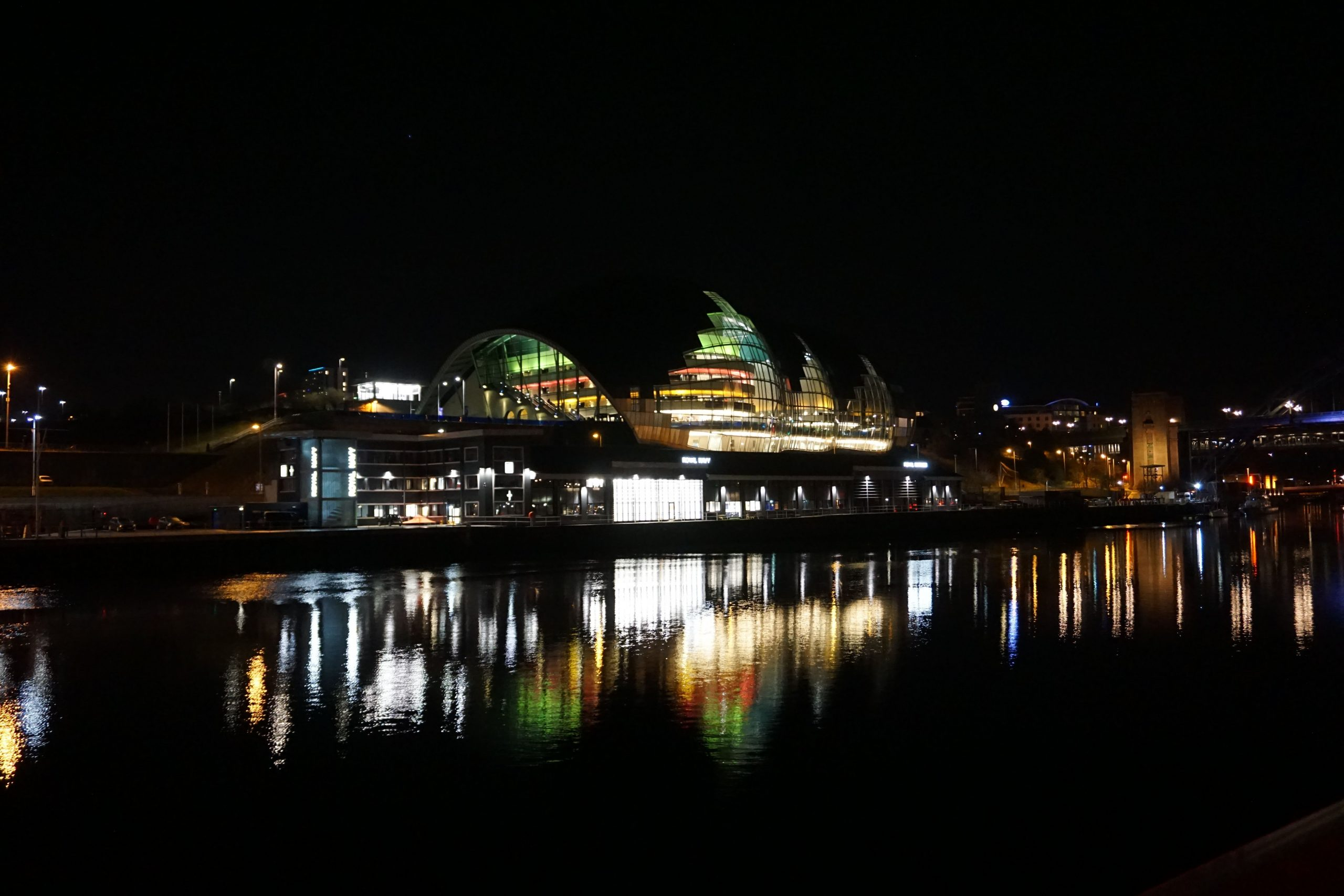 Gateshead Sage building from across the river, the colored lights are reflected in the river Tyne.