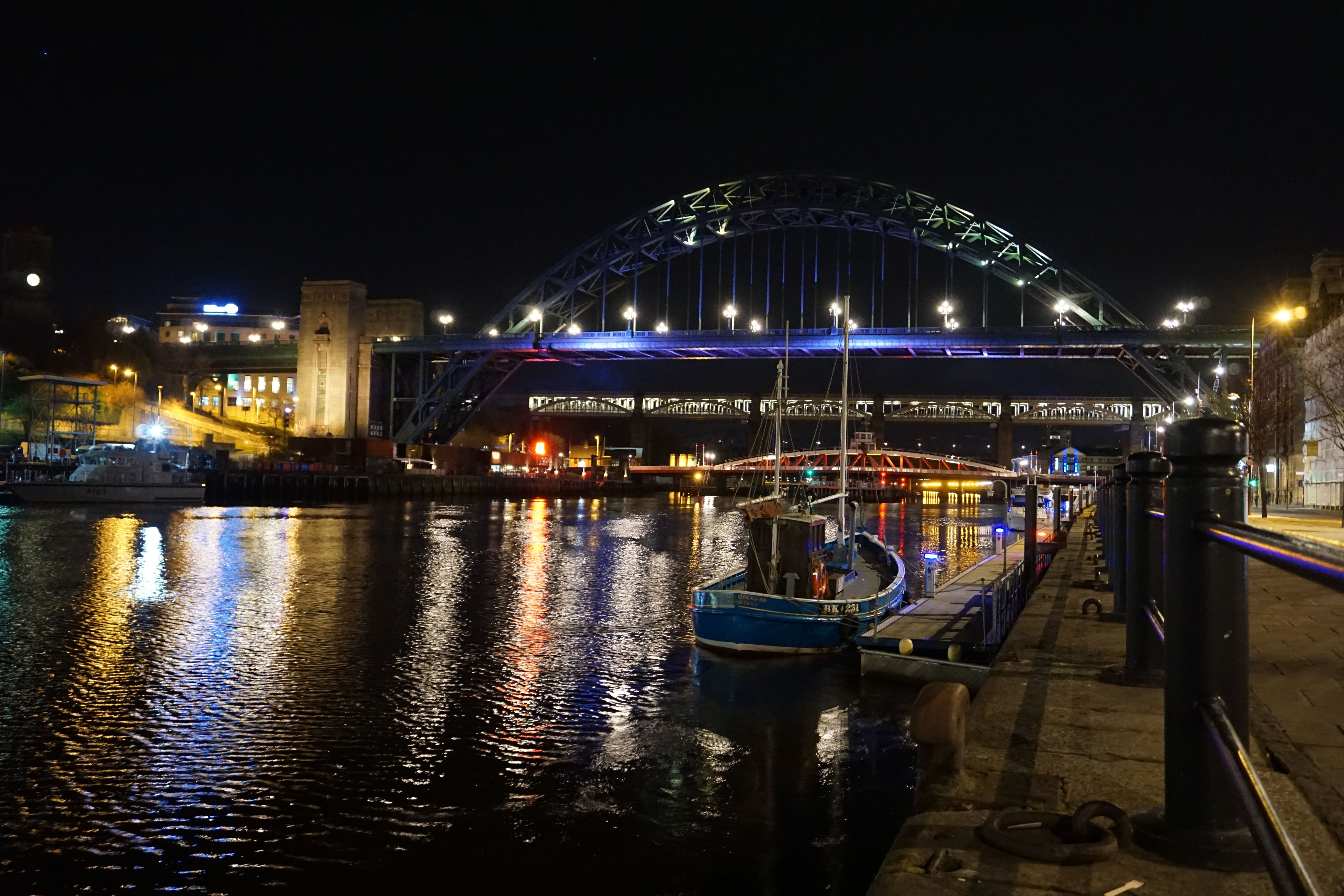 A small boat is moored in the River Tyne at night, the background has the Tyne Bridge. Lights are reflected in the water.