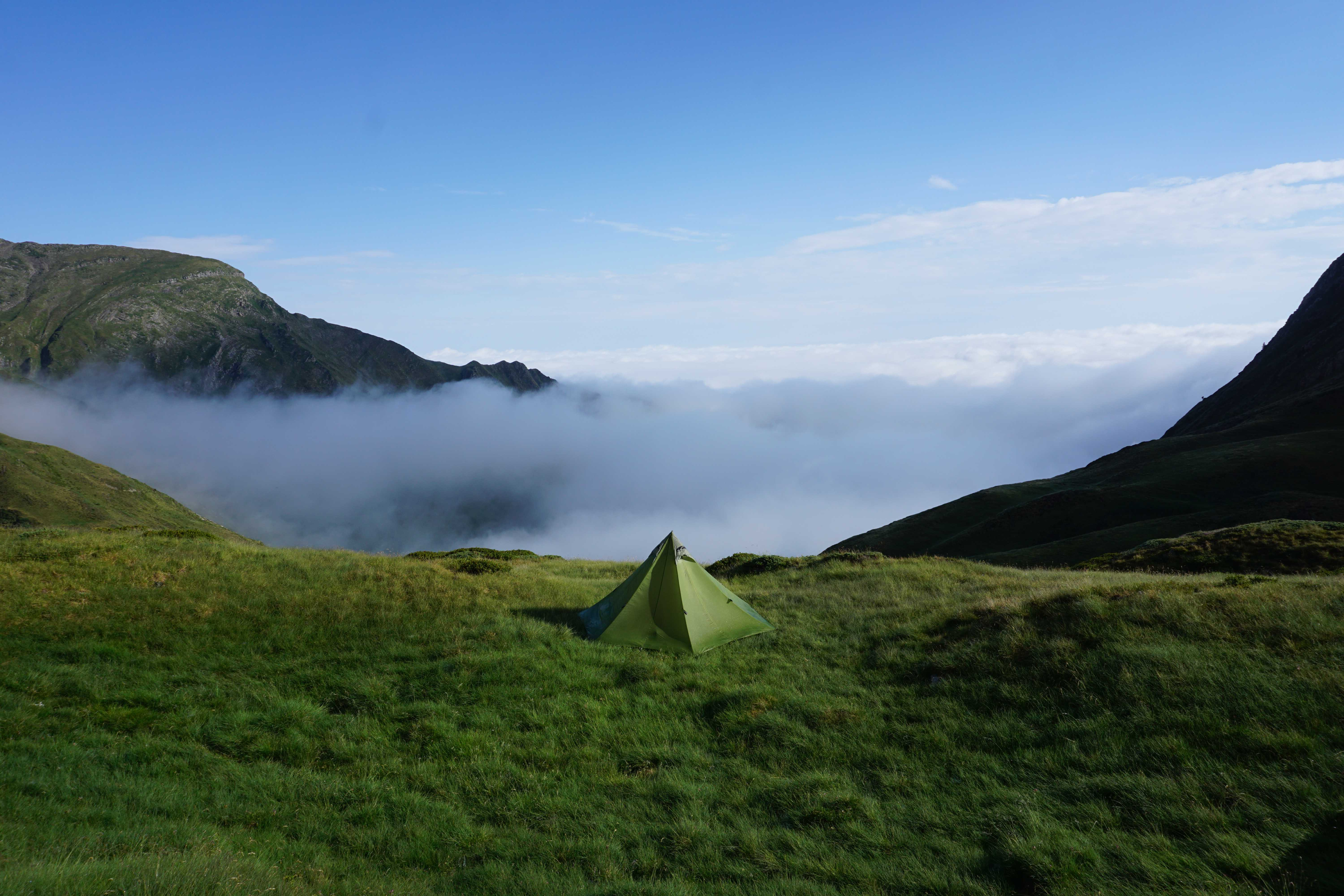 Triangular go light tent pitched on a mountain with cloud in the valley below