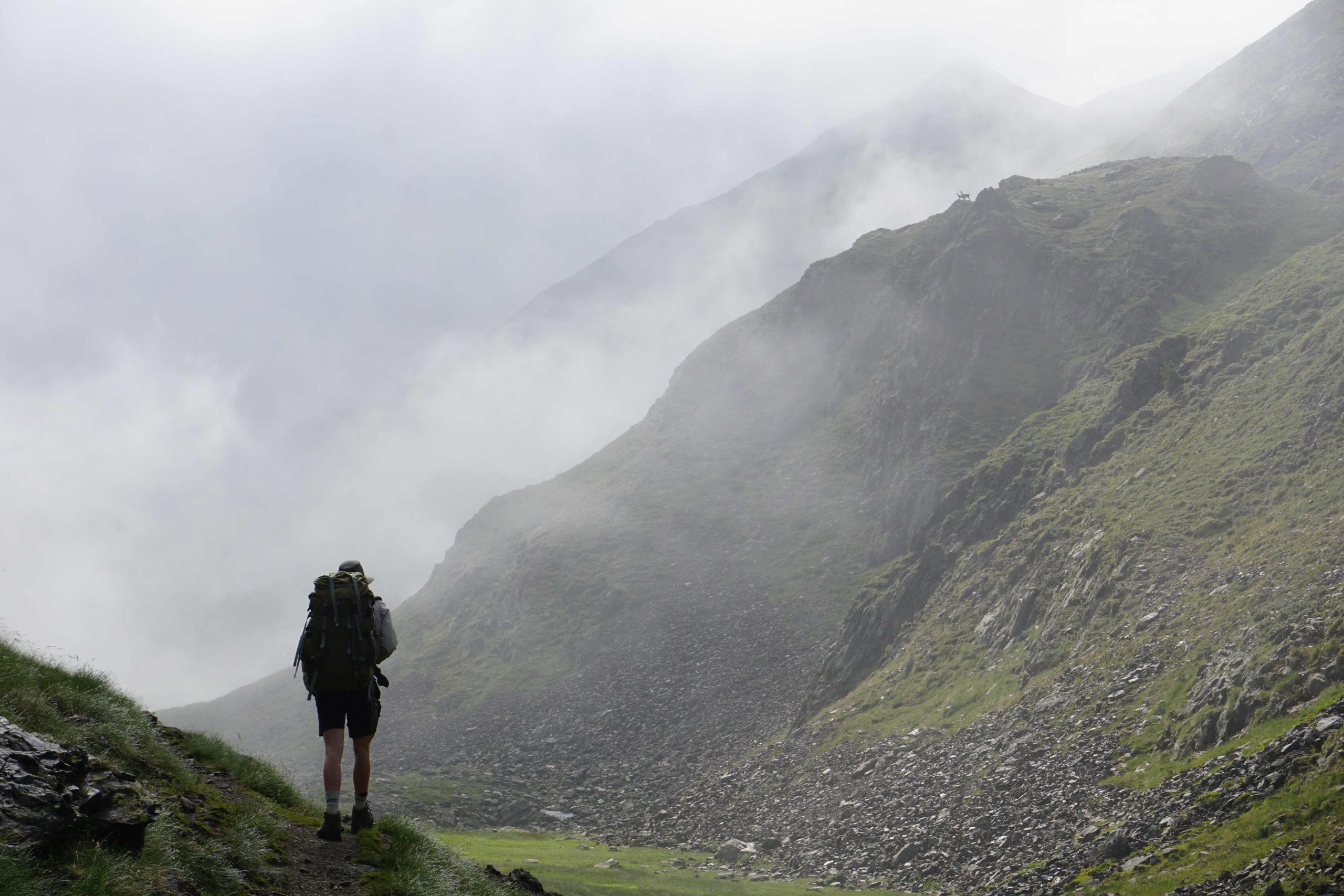 Man in hiking clothes walking into a misty mountain valley