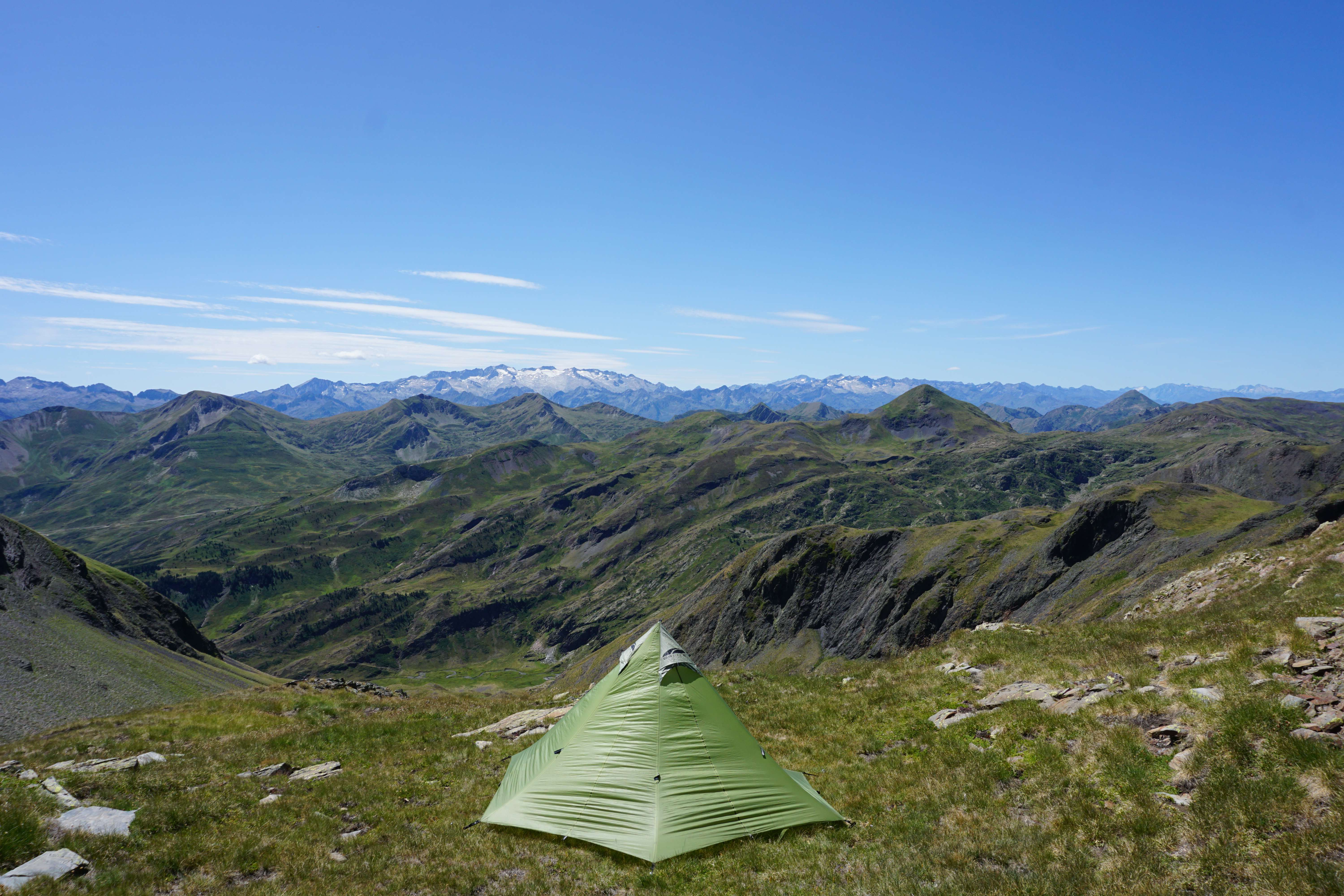Triangular go light tent pitched on the edge of a cliff infront of large mountains